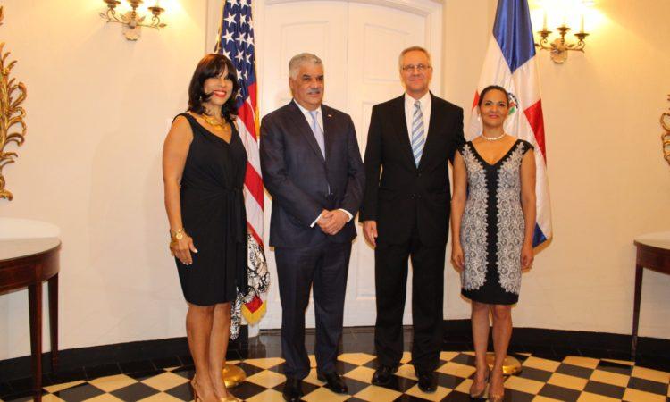 Dos hombres y dos mujeres posando frente a banderas de Estados Unidos y República Dominicana