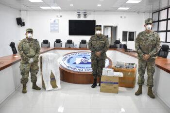 Tres personas con uniformes militares, con cajas cerca de ellos.