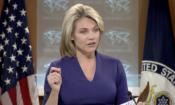 una mujer hablando en un podio, con la bandera de los Estados Unidos y el Departamento de Estado detrás.