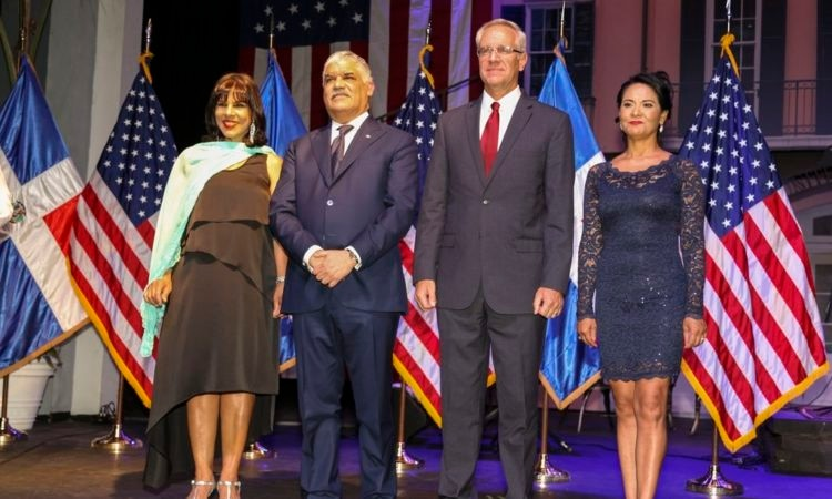 Two men and two women on a stage, in front of U.S. and Dominican Republic flags.