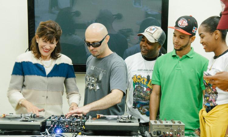 Una mujer y un hombre utilizan un equipo de música mientras tres jóvenes observan.