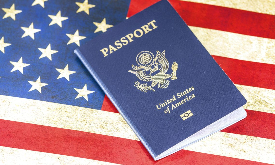 A US passport in front of an American flag