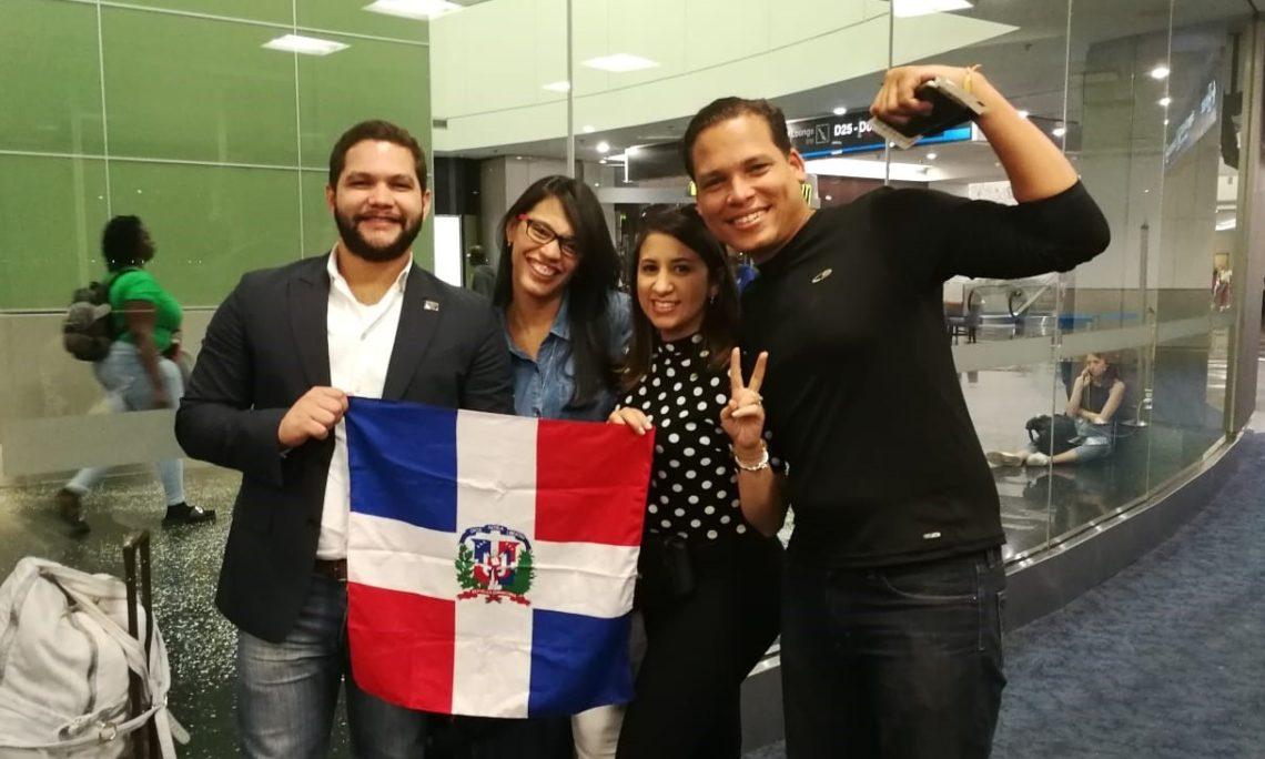four young students holding a dominican flag and smiling
